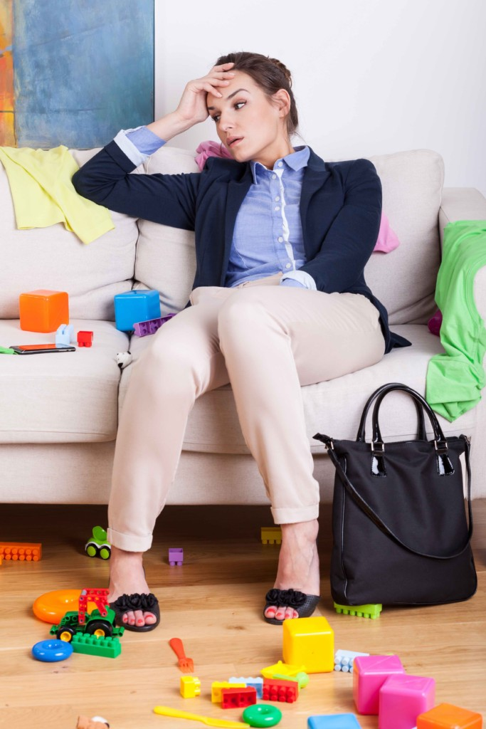 Tired mother sitting on sofa after hard day at work